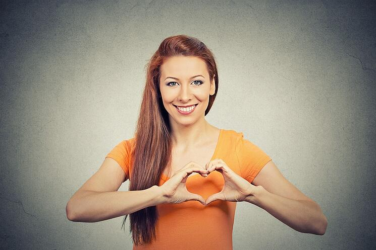 Closeup portrait smiling cheerful happy young woman making heart sign with hands isolated grey wall background. Positive human emotion expression feeling life perception attitude body language.jpeg